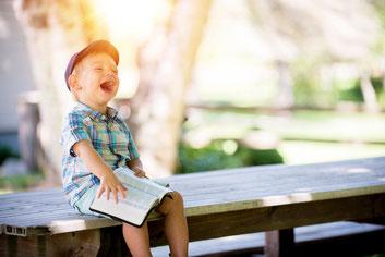 Bild: lachender Junge mit Buch